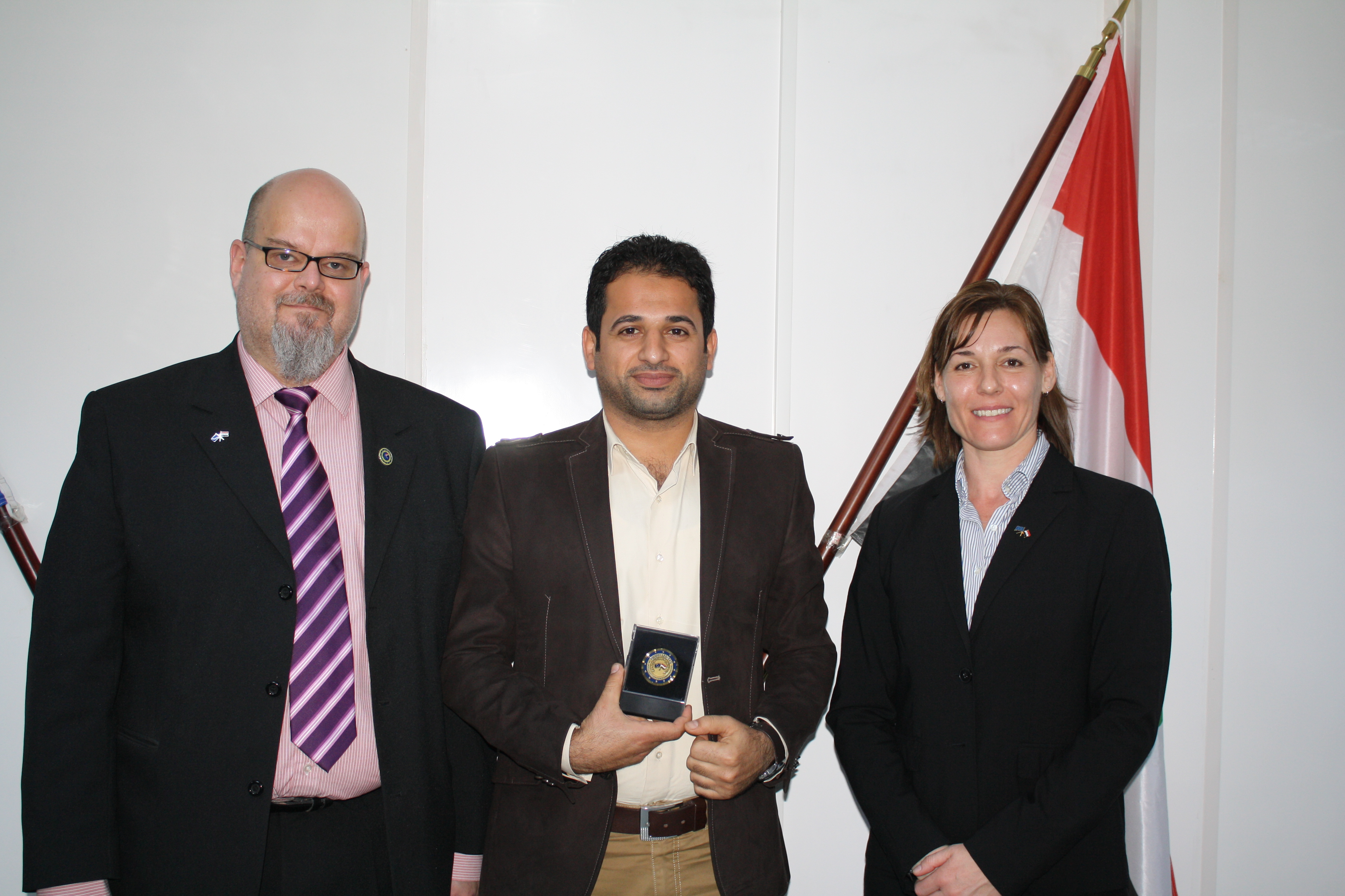 Haider Malik receiving a special coin for his first role as ISAP co-Trainer from Alison Stables. Matti Virkunnen looks on