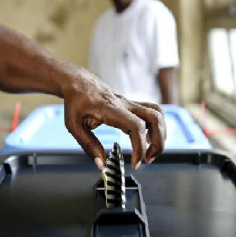 Hand dropping a voting paper into a ballot box while a man watches