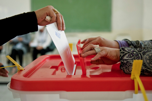 Hand putting voting card into ballot box, other hands hold open ballot box