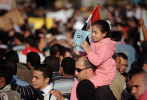 A young girl holding an Egyptian flag and sitting on a man's shoulder's in a crowd © Reporters